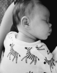 A photo of baby Florence who is wearing a baby grow, which is covered in zebras.